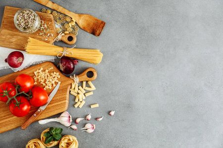 Spaghetti and fettuccine with ingredients for cooking pasta on cement backdrop with blank of wooden kitchen board, top view. Rustic style. Flat lay with space for text