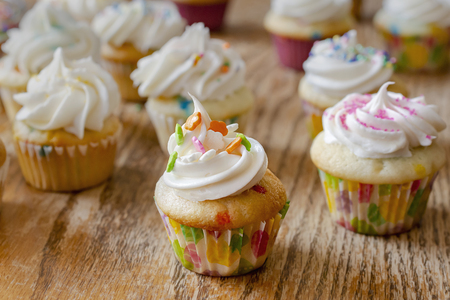 Various mini cupcakes decorated in spring and Easter colors. Background of a rough wood table.