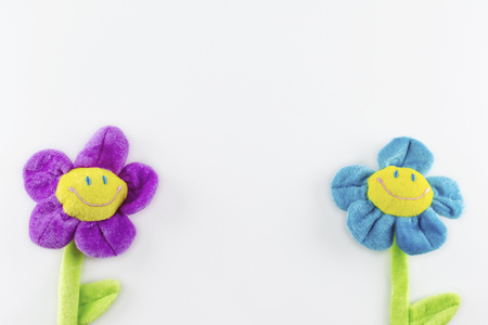 Two toy plush smiling flowers on a white background, one on each side.  Copy space in the middle and above.