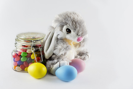 Stuffed toy easter bunny with colorful dyed eggs and a glass jar filled with jelly beans on a white background.  Copy space to the right.