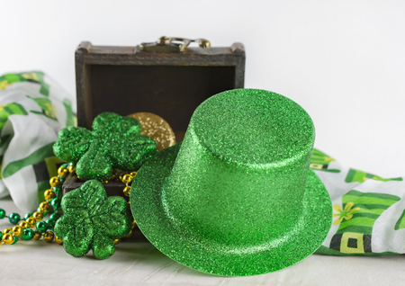 Saint Patrick's Day treasure chest filled with coins and beads. Close up view of green top hat leaning against chest. Colorful scarf in background. White background.