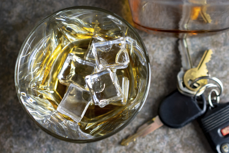 Close up shot of a brandy glass with ice.  Keys and bottle blurred in the background.  Shot against a neutral background.