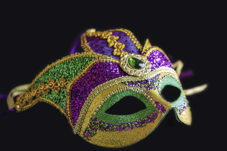 Jester mask lying on black background.  Close up view of the full mask.
