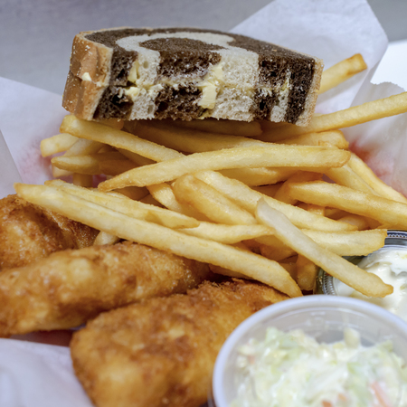 Bar Food: Typical Friday night fish fry in Wisconsin. Fried cod, french fries, coleslaw, tartar sauce and marbled rye bread in a basket. Stock Photo