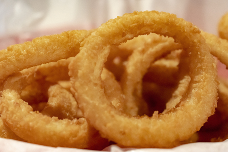 Close up view of deep friend  golden onion rings in a basket with white paper liner.