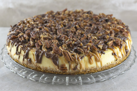 Close up view of a turtle cheesecake on a glass platter.  Horizontal crop.  Blurry background.  Neutral colors.