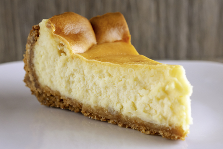 Close up view of a slice of plain cheesecake on a white plate.  Side view.  Wooden background blurred. 스톡 콘텐츠