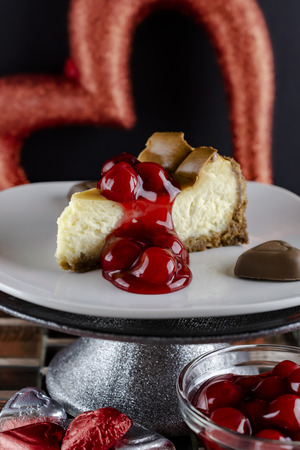 Piece of cherry cheesecake on a cake pedastal with chocolate hearts below and a bowl of cherry sauce.  Black background with red heart.