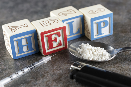 Help spelled out in blocks with a syringe and spoon with white powder (wheat flour depicting illegal drugs) and a lighter.