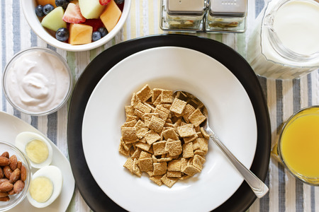 A bowl of cereal as part of a balanced breakfast.  Includes:  Yogurt, almonds, hard boiled egg, mixed fruit, orange juice, and milk.  Flat lay, over head shot.  Background of a striped place mat.