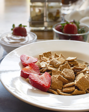 A bowl of cereal with strawberries as part of a balanced breakfast.  Yogurt, eggs, and strawberries blurred in the background.