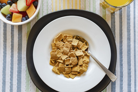 Flat lay of a bowl of cereal with a bowl of mixed fruit in the upper left corner and a glass of orange juice in upper right.  Background of striped multicolored place mat. 스톡 콘텐츠