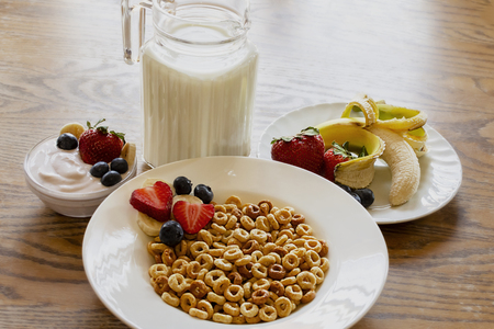 Bowl of oat cereal on a wooden table with yogurt, milk, strawberries, blueberries, and banana.