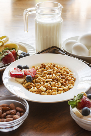 A bowl of oat cereal with a plate of fruit, yogurt, hard boiled eggs, and almonds on a wooden tray. 스톡 콘텐츠
