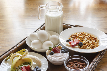 A bowl of oat cereal on a wooden tray with yogurt, hard boiled eggs, banana, strawberries, blueberries, milk and almonds.
