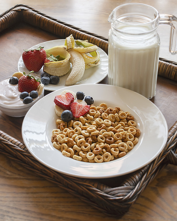 A bowl of oat cereal on a wooden tray with assorted fruit, yogurt, and small pitcher of milk.  Wooden tray at an angle.  Tight vertical crop. 스톡 콘텐츠
