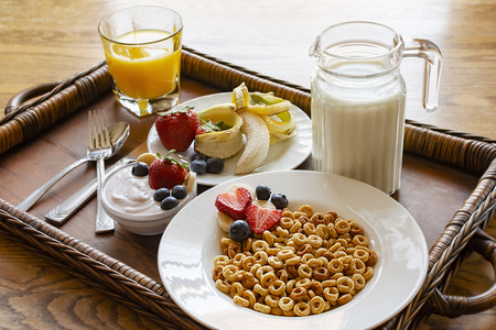 A bowl of oat cereal on wooden tray with assorted fruit, yogurt, orange juice and milk.  Tray on wooden table.  Angled side view.