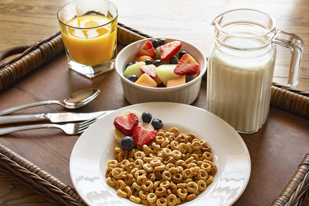A bowl of oat cereal with fruit and milk on a wooden tray on a wood table.  A bowl of mixed fruit in background with a glass of orange juice and a pitcher of milk.
