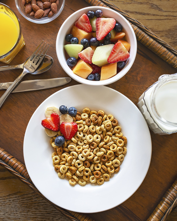 Flat lay of a bowl of oat cereal with fruit, nuts, orange juice and milk on wooden tray.  Tray is on a wooden table.  Silverware included.