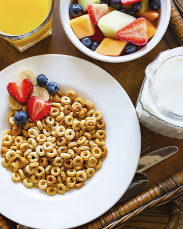 A bowl of oat cereal with assorted fruit bowl, orange juice, and milk on a wooden tray. 스톡 콘텐츠