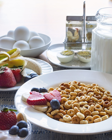 A bowl oat cereal with fruit, milk, eggs and yogurt as part of a balanced breakfast. Zdjęcie Seryjne