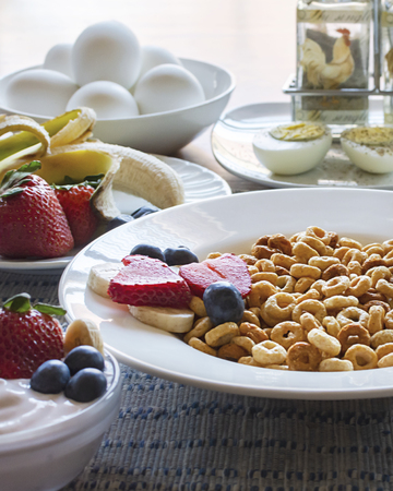A bowl of oat cereal with bananas, strawberries, and blueberries.  Hard-boiled eggs and salt and pepper shaker blurred in the background.