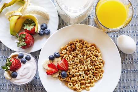 Flat lay of a bowl of oat cereal with bananas, strawberries, and blueberries.  Additional yogurt, hard boiled egg, milk, and orange juice featured as well.  Blue and white place mat as a background.