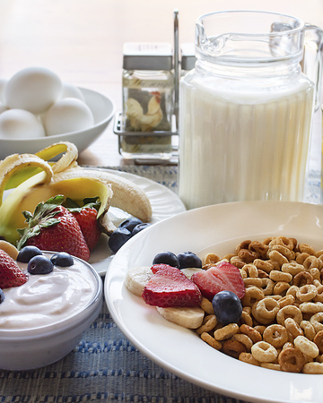 A bowl of oat cereal with various fruits, including banana, strawberries, and blueberries.  Bowl of yogurt and hard boiled eggs as well with a pitcher of milk, salt and pepper shakers.