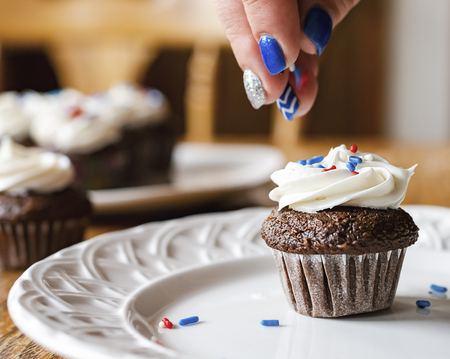 Mini cupcake being sprinkled with red, white, and blue sprinkles.  Blurred cupcakes in the background.