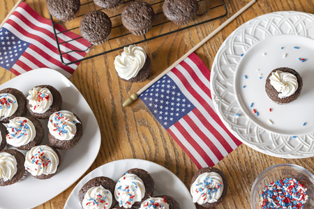 Overhead shot of mini cupcakes with white frosting and red, white, and blue sprinkles.  Additional cupcakes unfrosted on wire rack.  Wooden table.  US flags on table as well.