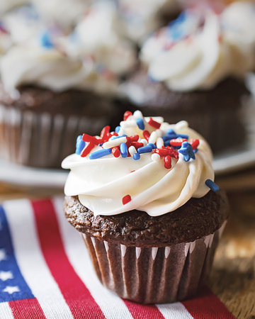 Close up of mini cupcake decorated with red, white, and blue sprinkles on a minature US flag.  Additional cupcakes blurred in the background. Imagens