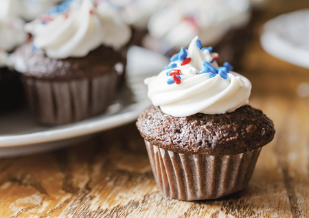 Mini cupcakes decorated in red, white, and blue sprinkles.  Blurred additional cupcakes in background.  Wooden table.