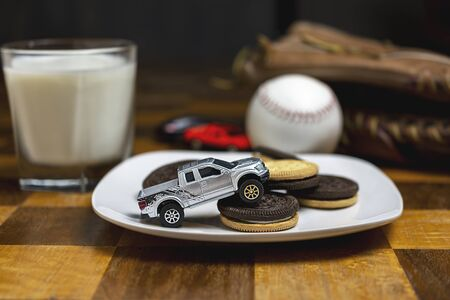 Toy truck driving over a plate of sandwich cookies.  Milk, ball and glove blurry in background.