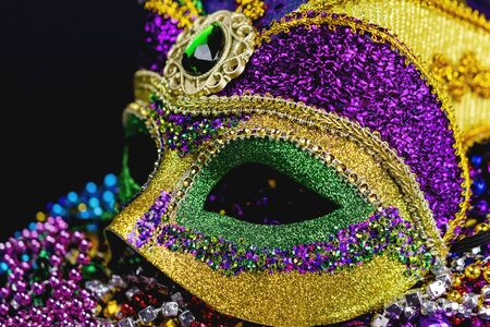 Front side view of a colorful jester mask on a bed of festival beads.