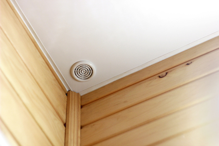 Fire alarm of fire detector on a ceiling. Smoke sensor in corner of room, wall of wood. Fire safety system