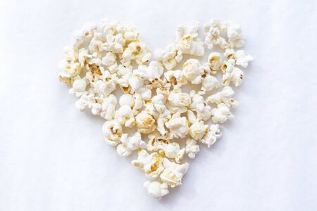 Tasty salted popcorn in shape of heart on white background. Top view minimalistic popcorn