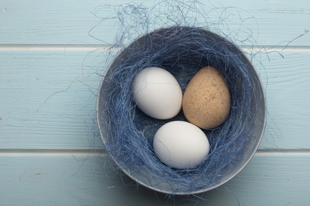 Three eggs in a dish with sisal on a blue wooden surface. Stock Photo
