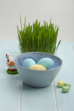 Easter eggs in a dish and a hen and sweets on a blue wooden surface. Banque d'images