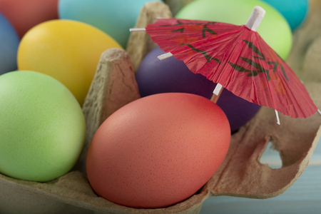 Colorful Easter eggs under umbrella in a carton are taking sunbath on the Easter weekend