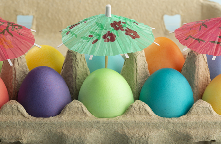 Colorful Easter eggs under umbrellas in a carton are taking sunbath on the Easter weekend