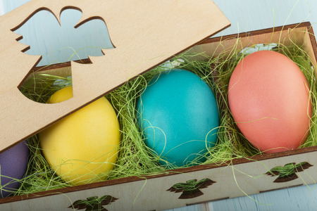 Mix of colorful Easter chicken eggs in a wooden box decorated with a green sisal.