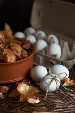 White eggs  in a box with a yellow onion peel  in a dish on a wicker tray prepared for coloring in natural dye on Easter holiday.