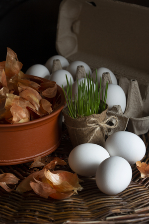 Natural spring grass in a pot, white eggs  in a box with a yellow onion peel  in a dish on a wicker tray prepared for coloring in organic dye on Easter holiday. Stock Photo