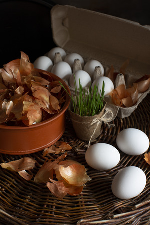 White eggs  in a box with a yellow onion peel  in a dish on a wicker tray prepared for coloring in organic dye on Easter holiday and natural spring grass in a pot.