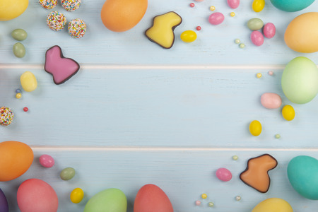 Ð¡hocolate bunnies, Easter dyed chicken eggs, variety of sweets and colorful dressing on the wooden blue background. Stock Photo