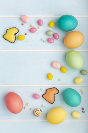 Easter colorful chicken eggs, chocolate bunnies, variety of sweets and colorful sprinkles on the wooden blue background. Stock Photo