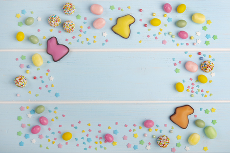 Easter colorful chocolate bunnies, variety of sweets and bright sprinkles on the wooden blue background.