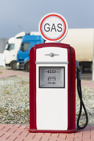 Red and white vintage gasoline fuel pump with cargo trucks in the background. Stock Photo