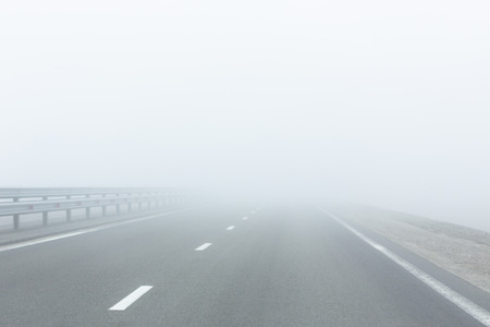 Perspective view of asphalt  empty road with guardrail and marking lines in a white fog in the morning.