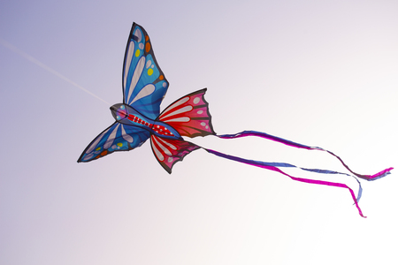 Colorful butterfly kite with bright ribbons is flying in the sky on the sunset.